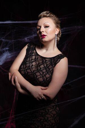 Woman in evening classic dress posing on black Halloween background with spider web Zdjęcie Seryjne - 136809835
