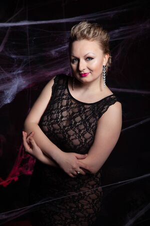 Woman in evening classic dress posing on black Halloween background with spider web Zdjęcie Seryjne - 136809853