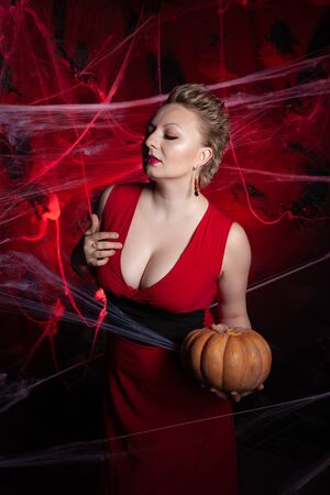 Woman in evening classic dress posing with pumpkin on black Halloween background with spider web Stok Fotoğraf