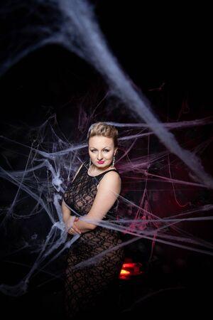 Woman in evening classic dress posing on black Halloween background with spider web Zdjęcie Seryjne - 136809866
