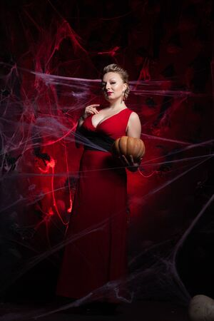 Woman in evening classic dress posing with pumpkin on black Halloween background with spider web Stock Photo