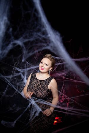 Woman in evening classic dress posing on black Halloween background with spider web Zdjęcie Seryjne - 136809875