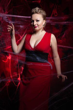 Woman in evening classic dress posing on black Halloween background with spider web Zdjęcie Seryjne - 136809916