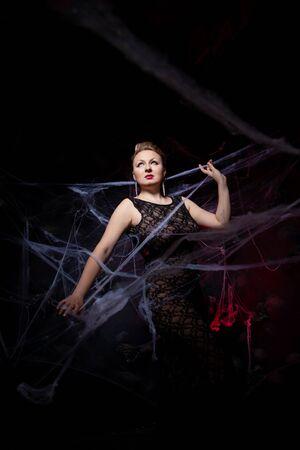 Woman in evening classic dress posing on black Halloween background with spider web Zdjęcie Seryjne - 136809940