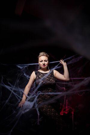 Woman in evening classic dress posing on black Halloween background with spider web Zdjęcie Seryjne - 136809942