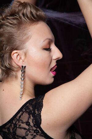 Woman in evening classic dress posing on black Halloween background with spider web Zdjęcie Seryjne - 136600448