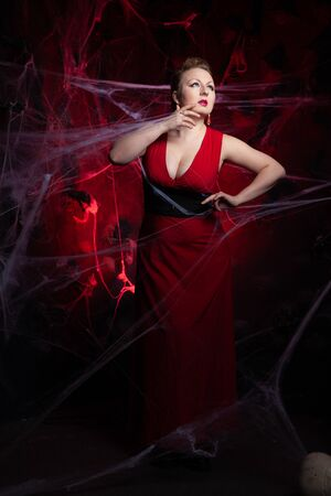 Woman in evening classic dress posing on black Halloween background with spider web