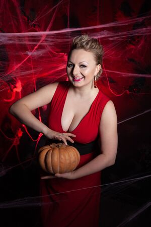 Woman in evening classic dress posing with pumpkin on black Halloween background with spider web Zdjęcie Seryjne - 136600458