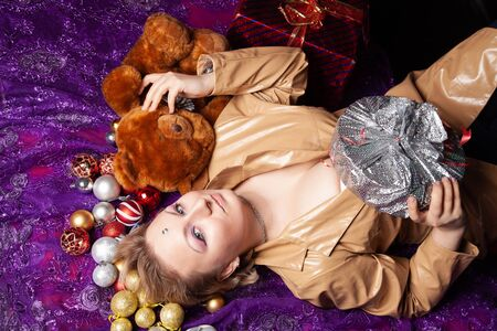 Top view of a young woman lying on the floor surrounded with nicely christmas toys balls and wrapped present Zdjęcie Seryjne