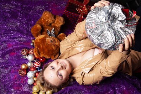 Top view of a young woman lying on the floor surrounded with nicely christmas toys balls and wrapped present Stock Photo - 136810250
