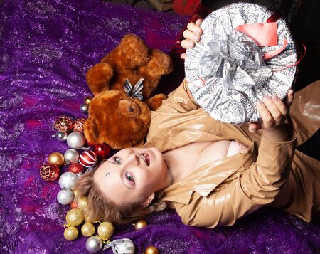 Top view of a young woman lying on the floor surrounded with nicely christmas toys balls and wrapped present Stock Photo