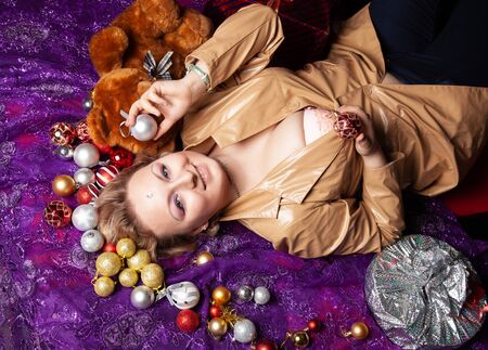 Top view of a young woman lying on the floor surrounded with nicely christmas toys balls and wrapped present Zdjęcie Seryjne - 136600730