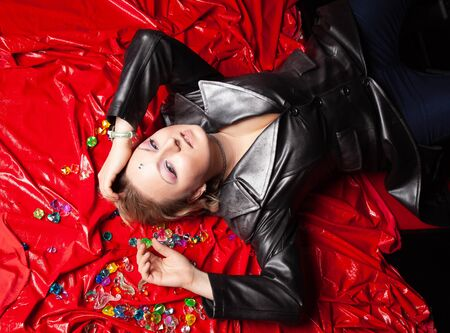 a beautiful plus size woman in leather clothes lies on a red vinyl bedspread. the view from the top. Stock Photo - 136810325