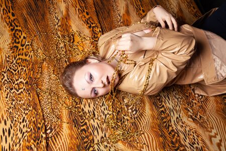 top view on charming plus size girl with short hair lies in leather beige jacket on a leopard print sheet Stock Photo - 136810356