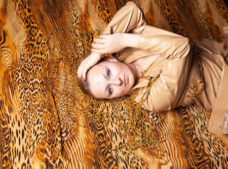 top view on charming plus size girl with short hair lies in leather beige jacket on a leopard print sheet Stock Photo - 136810359
