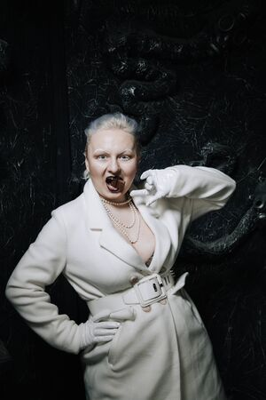 Young freak plus size albino woman greedily eats and love chocolate on black background. curvy short hair girl in white outfit.