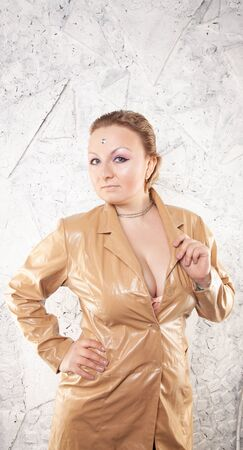 adult woman in beige leather jacket portrait on white wall background
