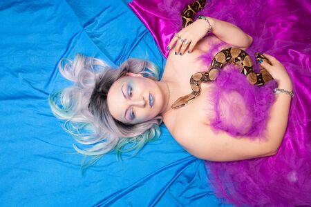 Young woman with grey hair and strange make up lies with snake. Top View of beautiful adult nude girl.