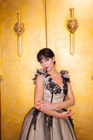 alluring sexy woman in evening dress posing over golden studio background Zdjęcie Seryjne - 136810522