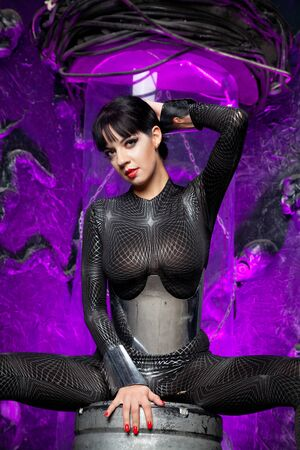Shot of a futuristic young person posing near glass space capsule with wires and purple neon light on black background Zdjęcie Seryjne - 136810540