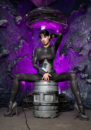 Shot of a futuristic young person posing near glass space capsule with wires and purple neon light on black background