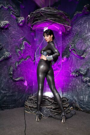 Shot of a futuristic young person posing near glass space capsule with wires and purple neon light on black background Zdjęcie Seryjne - 136810548