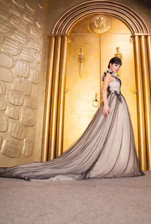 alluring sexy full length woman in evening dress posing over golden studio background Zdjęcie Seryjne - 136810550