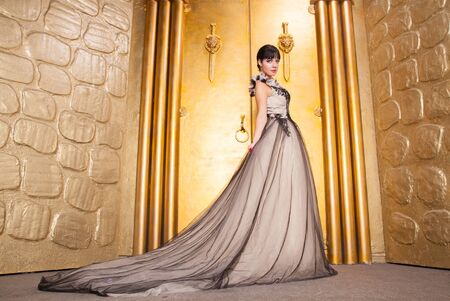 alluring sexy full length woman in evening dress posing over golden studio background Stock Photo - 136810551