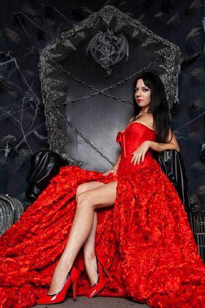 beautiful vampire woman in red long dress near big black throne in the studio