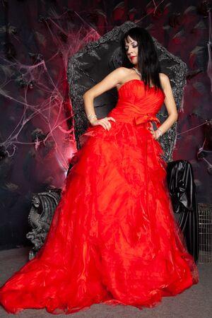 beautiful vampire woman in red long dress near big black throne in the studio Standard-Bild