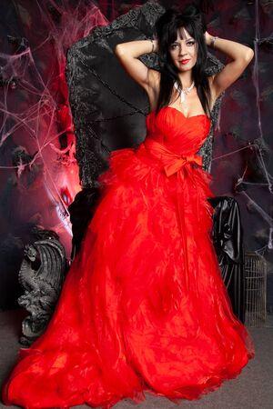 beautiful vampire woman in red long dress near big black throne in the studio Stock Photo - 137669581