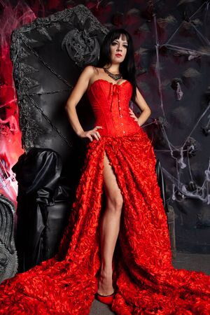 beautiful vampire woman in red long dress near big black throne in the studio Stock Photo - 137669582