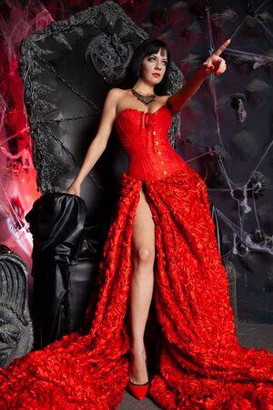 beautiful vampire woman in red long dress near big black throne in the studio Stock Photo - 137669594