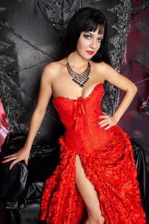 beautiful vampire woman in red long dress near big black throne in the studio Stock Photo - 137669595