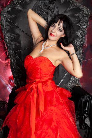 beautiful vampire woman in red long dress near big black throne in the studio Zdjęcie Seryjne - 136810605