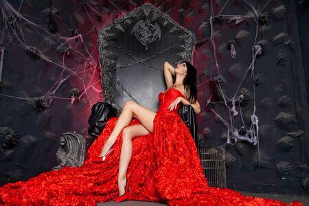 bella donna vampiro in abito lungo rosso vicino al grande trono nero in studio Archivio Fotografico