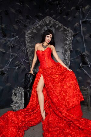 beautiful vampire woman in red long dress near big black throne in the studio