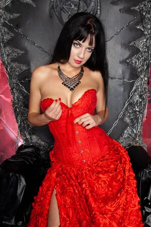beautiful vampire woman in red long dress near big black throne in the studio Zdjęcie Seryjne - 136810629