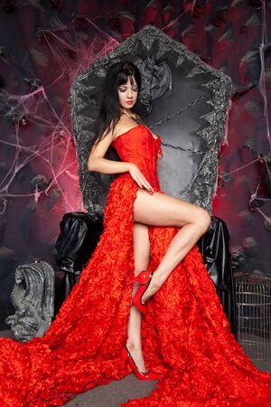 beautiful vampire woman in red long dress near big black throne in the studio Zdjęcie Seryjne - 136810631