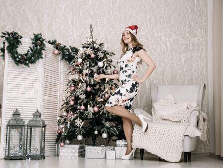 Mooie vrouw in witte strakke jurk en rode kerstmuts binnenshuis in de buurt van versierde dennenboom alleen Stockfoto
