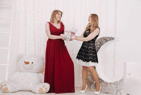 a pregnant woman in an evening red dress stands next to a friend in the nursery of her unborn child Stock Photo