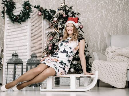 Pretty woman in white tight dress and red santa hat indoors near decorated fir tree alone 版權商用圖片