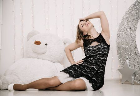 pretty adult girl with big white teddy bear alone