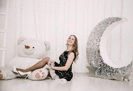 mooi volwassen meisje met alleen een grote witte teddybeer Stockfoto