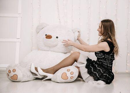 Bonita chica adulta con gran oso de peluche blanco solo Foto de archivo