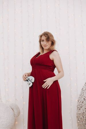 Young beautiful stylish pregnant woman in red long evening dress on white background of child room Stock Photo