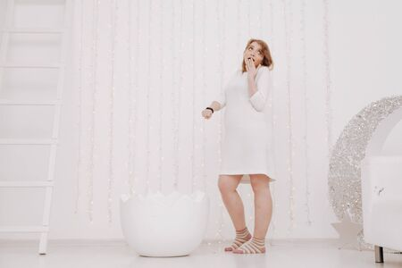 a pregnant woman at 9 months stands near a huge broken eggshell and waits for the baby to appear on a white background