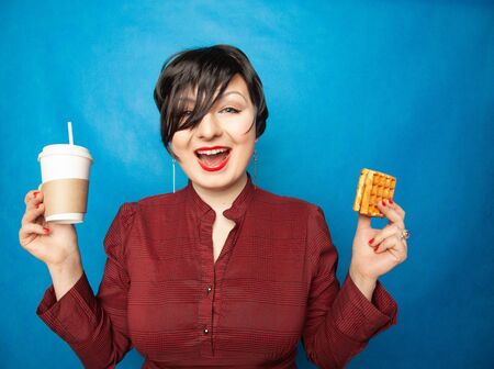 joyful plus size woman with short hair in business clothes resting and drinking coffee with a straw with Viennese waffle as snack on a blue studio background. Stock fotó
