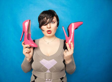 happy brunette girl loves her beautiful bright pink shoes. plus size woman with short hair holds beautiful high heels shoes in her hands and enjoys Banco de Imagens