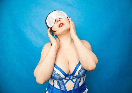 charming happy plus size woman with white blindfold in beautiful lingerie posing on a blue background in the Studio